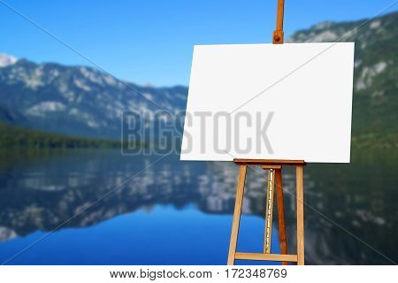 Blank painter artist canvas on easel with lake in background copy space for artistic picture or painting
