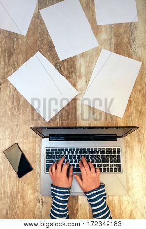 Creative female person working on laptop computer in the office top view of hands typing keyboard on desk with smartphone and papers scattered around