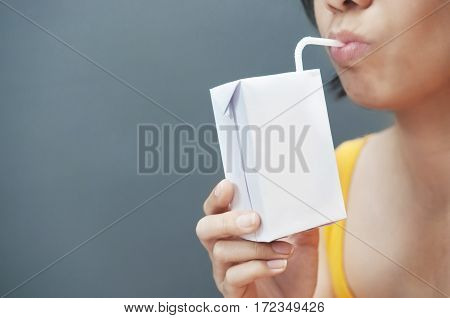 Asian woman drinking milk with copy space. Milk carton.