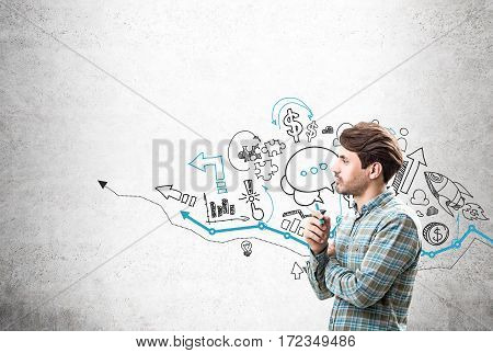 Bearded businessman is standing near a concrete wall with blue and black arrow sketch drawn on it. Concept of a start up.