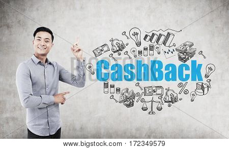 Portrait of an Asian man standing with a finger in the air near a concrete wall with a blue cash back drawing on it.