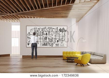 White living room interior with yellow and gray sofas white walls large panoramic window and a whiteboard. Man is drawing a poster on it. 3d rendering. Mock up.