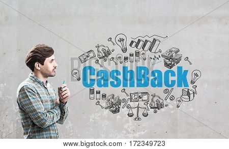 Side view of a man in a checkered shirt standing near a concrete wall with a blue cash back sketch drawn on it.