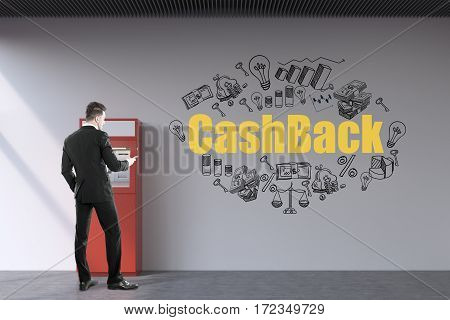 Rear view of a bearded businessman wearing a black suit who is withdrawing money from a red atm machine. There is a yellow cash back sketch on the wall.