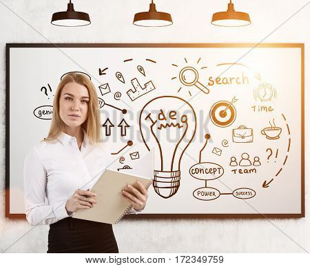 Portrait of a blond woman holding a large white notebook and standing near an idea sketch drawn on a whiteboard. Toned image.