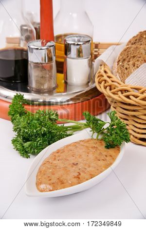 Thick Walnut Sauce In White Gravy Boat Decorated With Parsley On A Background Of Spices And Bread