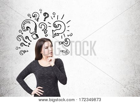 Portrait of a girl in a black dress standing near a concrete wall and thinking about a challenging problem. Question mark. Mock up.