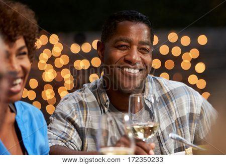 Group Of Mature Friends Enjoying Outdoor Meal In Backyard