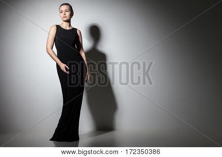 beautiful woman model posing in elegant black dress in the studio