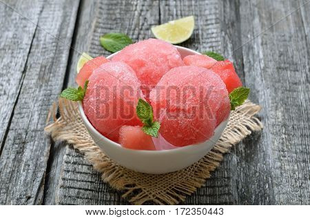 Watermelon ice cream with slices in bowl on wooden table