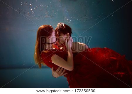 Underwater in the pool with the purest water. Loving couple hugging. The feeling of love and closeness. Soft