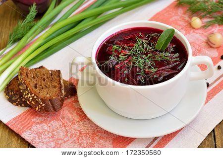 Beetroot soup borscht in white bowl on napkin