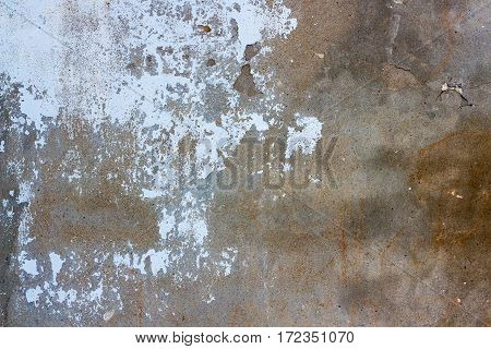 Old wall with peeling white paint. Many spots and also chips and cracks.