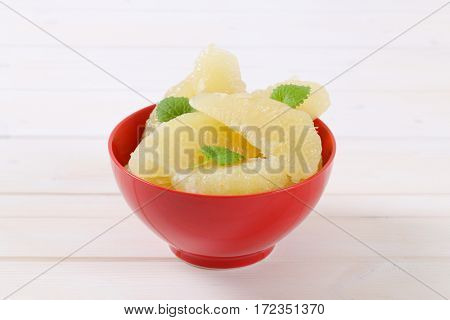 bowl of peeled and sliced pomelo on white background