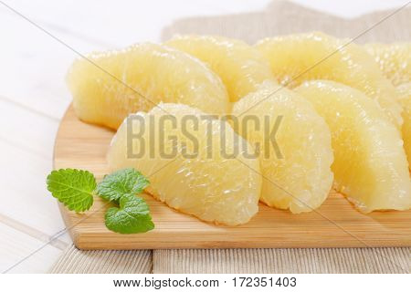 peeled and sliced pomelo on wooden cutting board - close up