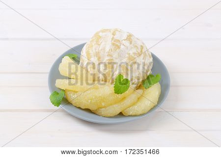 plate of peeled and sliced pomelo on white background