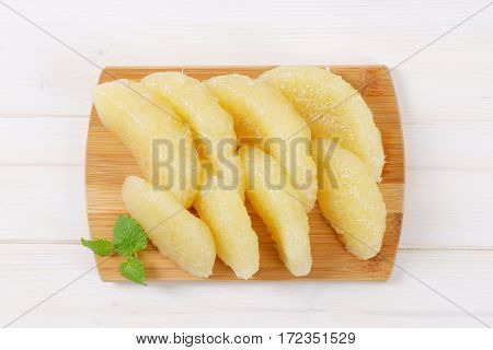 peeled and sliced pomelo on wooden cutting board
