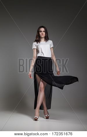 Beautiful model in white blouse and black skirt posing on grey background