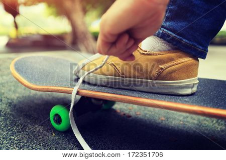 young skateboarder tying shoelace at city skatepark