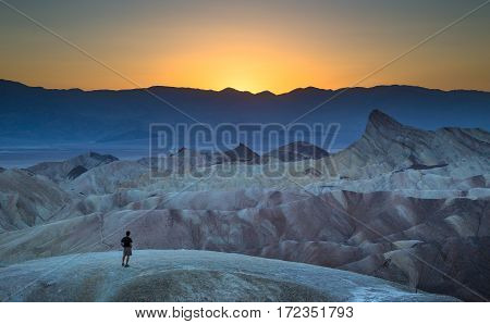 Man Enjoying Sunset At Famous Zabriskie Point, Death Valley National Park, California, Usa
