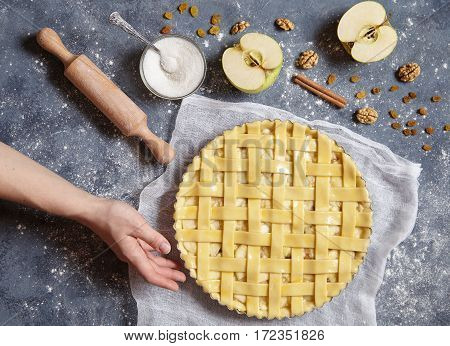 Apple pie tart traditional autumn sweet pastry baked food woman cooking recipe with ingridients, rolling pin, egg yolk, sugar flat lay on blue vintage background, top view
