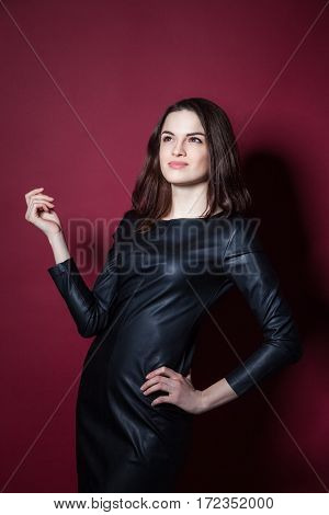 Young beautiful model posing in leather dress on red background