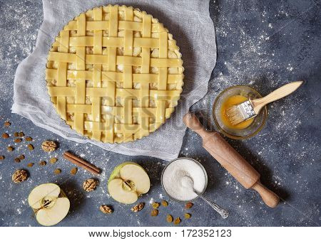 Apple pie tart traditional sweet pastry baked food woman cooking recipe with ingridients, rolling pin, egg yolk, sugar flat lay on blue vintage background, top view