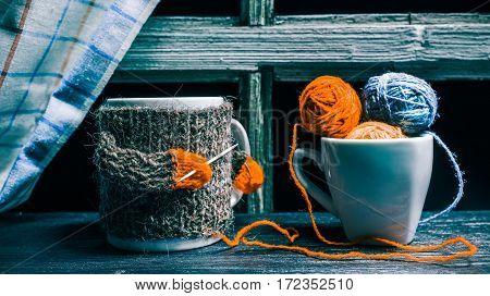 Wool balls in tea cup. Big mug in wool sweater knitting with toothpicks