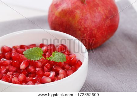 ripe pomegranate with bowl of seeds on grey place mat - close up