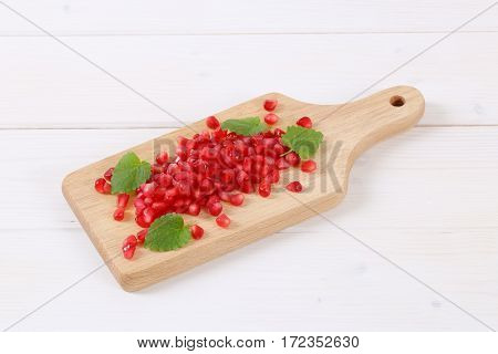 pile of pomegranate seeds on wooden cutting board