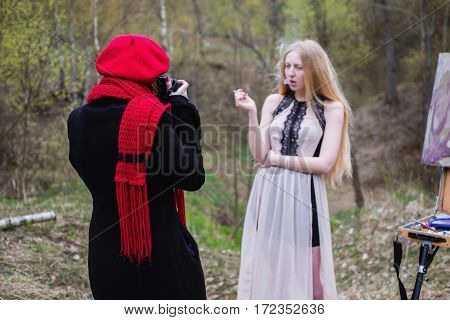 Blonde girl in a dress with a cigarette in hand smoking woman. A woman in a red beret and scarf making photos. Photographer at work.