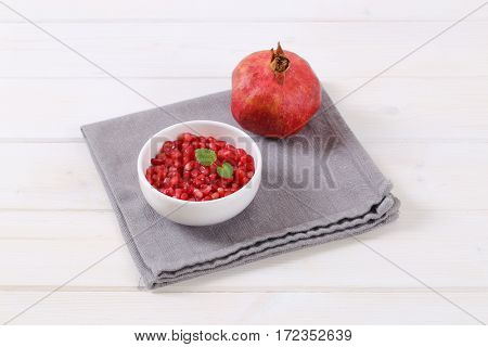 ripe pomegranate with bowl of seeds on grey place mat