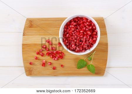 bowl of pomegranate seeds on wooden cutting board