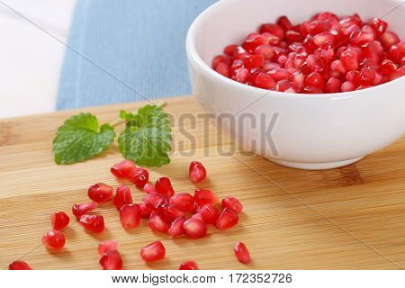 bowl of pomegranate seeds on wooden cutting board - close up