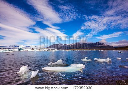 The ice floes and clouds of lagoon Jokulsarlon, Iceland. Clouds cirrocumulus reflected in the water of lagoon. The concept of northern extreme tourism