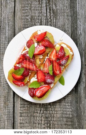 Bruschetta with strawberries and kiwi on white plate top view