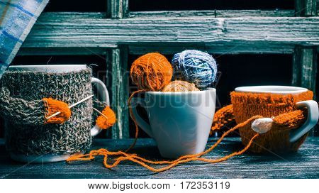 Wool balls in tea cup. Big mug and small cup in wool sweaters knitting with toothpicks