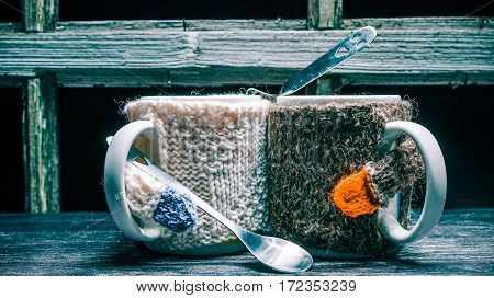 Romantic or friendly pair of mugs in sweaters holding teaspoons
