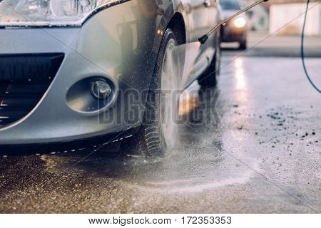Doing car wash under high pressure water.