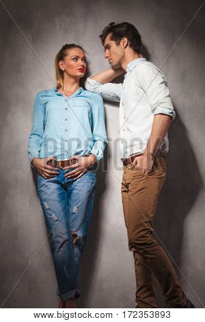 young casual man leaning on his woman and look at each other while posing in studio