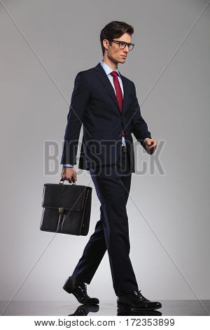 young businessman wearing glasses and suitcase is walking, side picture in studio