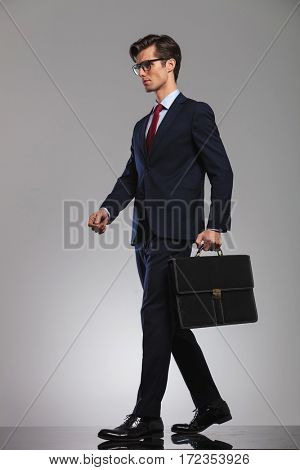 side view of an elegant businessman holding briefcase and walking in grey studio background