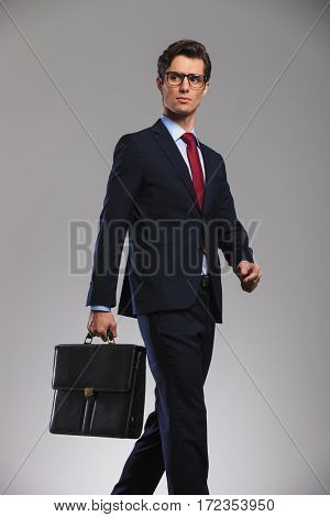 side portrait of a walking business man holding a suitcase and looks away from the camera in studio
