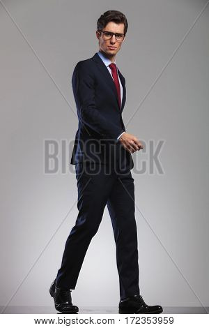 full body picture of a walking business man looking at the camera, side view in studio