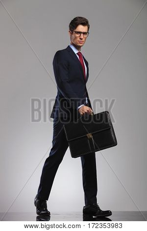 serious business holding a briefcase walks forward with confidence  in studio