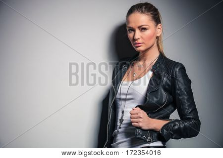 cute blonde woman in leather jacket holds her collar and looks at the camera
