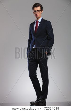 full body picture of a young business man standing with hands in pockets on grey studio background