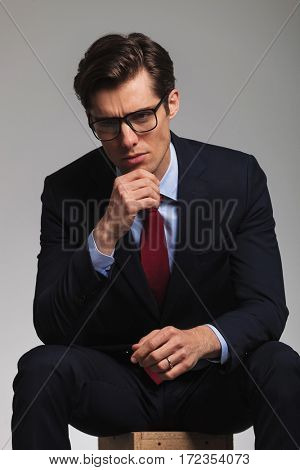 business man is resting on a chair and thinks of something on grey studio backgorund