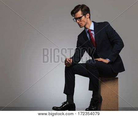side view of a sitting businessman wearing glasses and looking away from the camera with copyspace