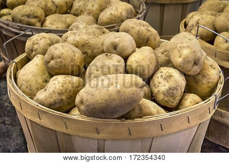 Potatoes piled into a natural wood basket are on sale at a produce market.